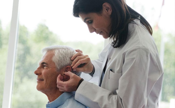 Audiologist checking mans ears