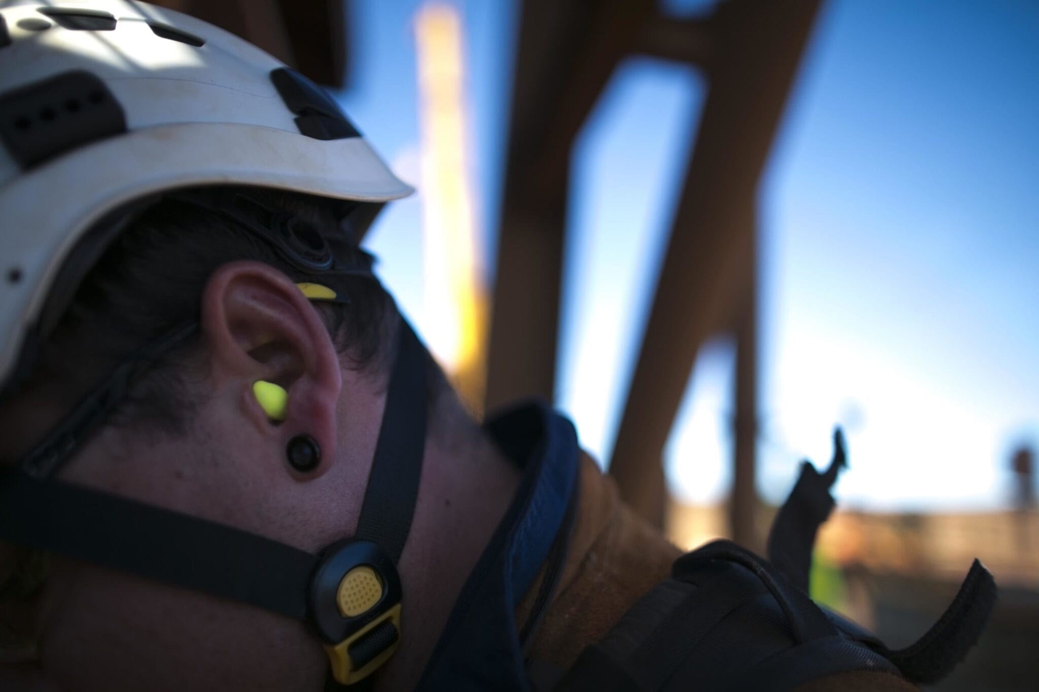 Miner worker wearing a ear plug noise safety protection when working near operating life plant machinery at construction site Perth, Australia